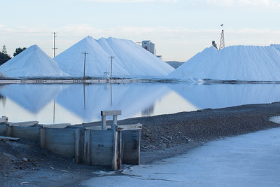 Salt Stockpiles with processing plant peering over the pile.